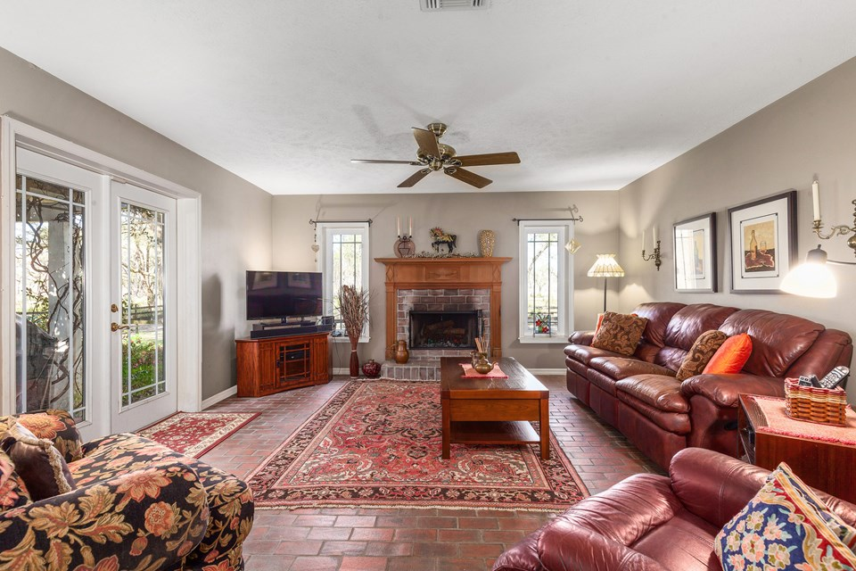 family room features a brick fireplace with an antique mantel