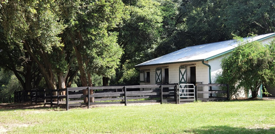 4-stall center aisle block barn with individual runouts, feed & tack rooms & indoor wash area