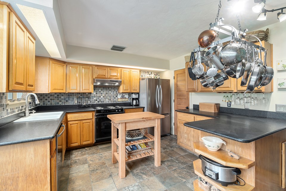 wood cabinetry, granite counters, stainless appliances and tiled floors in the kitchen