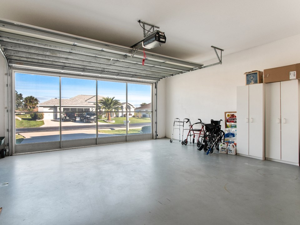 large 2-car garage with an extra tall ceiling, screened doors & painted floor